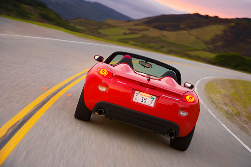 AUT 29 RK1292 01 © Kimball Stock 2007 Pontiac Solstice GXP Convertible Red Rear View On Road In Motion