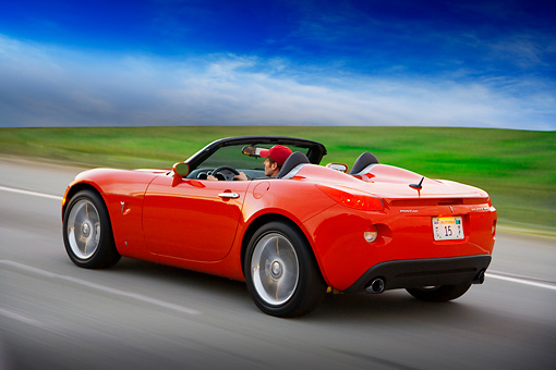 AUT 29 RK1295 01 © Kimball Stock 2007 Pontiac Solstice GXP Convertible Red 3/4 Rear View On Road In Motion