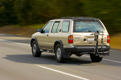 AUT 29 RK1324 01 © Kimball Stock 2004 Nissan Pathfinder Gold 3/4 Rear View On Road In Motion