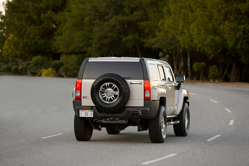 AUT 29 RK1365 01 © Kimball Stock 2007 Hummer H3 Silver 3/4 Rear View On Road In Motion By Trees