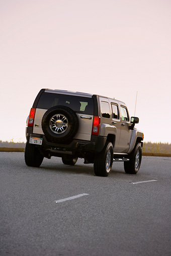 AUT 29 RK1369 01 © Kimball Stock 2007 Hummer H3 Silver 3/4 Rear View On Road In Motion At Dusk