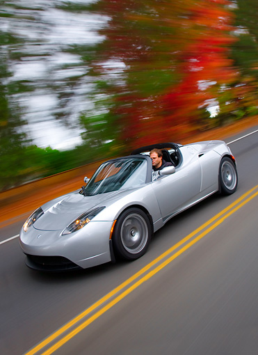 AUT 29 RK1460 01 © Kimball Stock 2008 Tesla Roadster Silver 3/4 Front View Driving By Autumn Trees