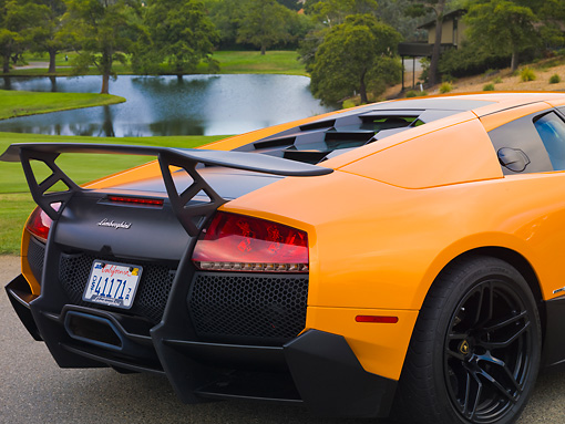 AUT 30 BK0019 01 © Kimball Stock 2010 Lamborghini Murci�lago LP670-4 SV Orange 3/4 Rear Detail On Pavement By Pond