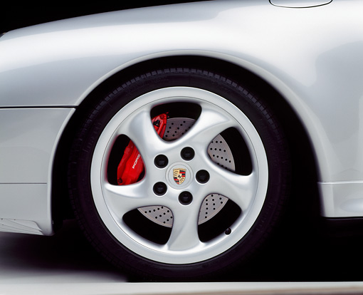 AUT 30 RK0121 07 © Kimball Stock 1998 Silver Porsche Detail Of Front Wheel With Red Brake Calipers