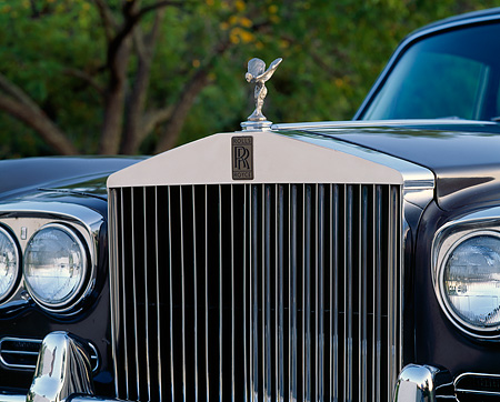 AUT 30 RK0322 07 © Kimball Stock Detail Of A 1972 Rolls-Royce Grill And Hood Ornament Trees Background