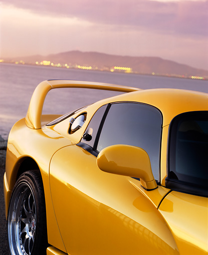 AUT 30 RK0429 02 © Kimball Stock 1996 Hennessey Viper Venom 650R Yellow Side Rear View By Water Mountains Dark Clouds
