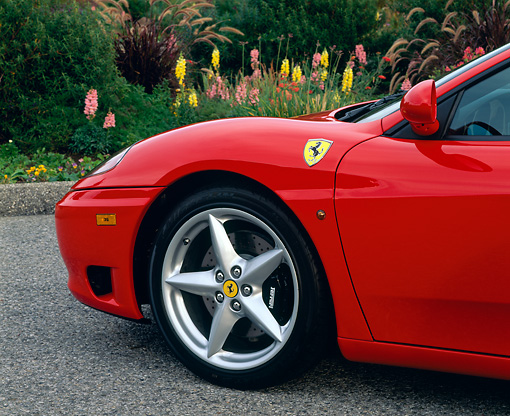 AUT 30 RK0468 02 © Kimball Stock 1999 Ferrari 360 Modena Red Detail Side Of Front Tire On Pavement By Flowers