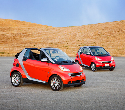 AUT 31 RK0103 01 © Kimball Stock 2009 Smart Fortwo Passion Cabriolet And Coupe Red And Silver 3/4 Front View On Pavement By Hills