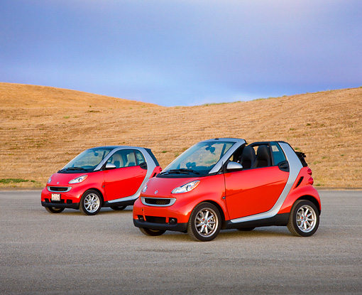AUT 31 RK0104 01 © Kimball Stock 2009 Smart Fortwo Passion Cabriolet And Coupe Red And Silver 3/4 Front View On Pavement By Hills
