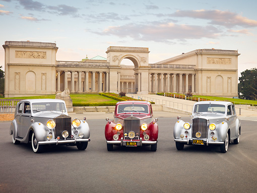 AUT 31 RK0106 01 © Kimball Stock 1948 Rolls-Royce Silver Wraith Silver, 1954 Rolls-Royce Silver Dawn Silver And Maroon, 1952 Bentley R Type Silver On Pavement By Building