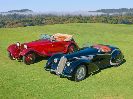 AUT 31 RK0109 01 © Kimball Stock 1937 Alfa Romeo 8C 2900B Spider Black And 1934 Alfa Romeo 8C 2300 Red 3/4 Front View On Grass