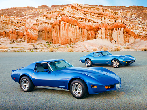 AUT 31 RK0112 01 © Kimball Stock 1975 And 1969 Chevrolet Corvettes Blue 3/4 Front View On Pavement By Red Rock