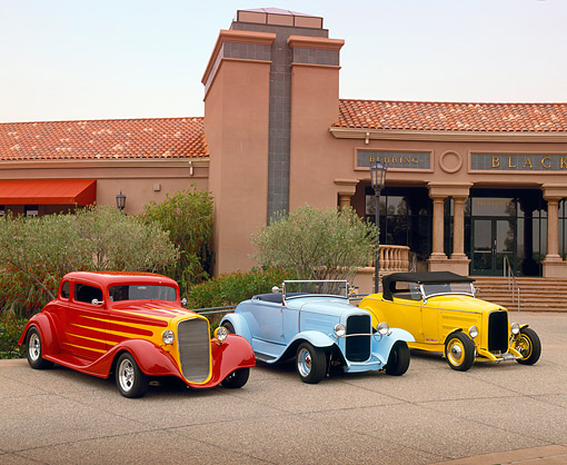AUT 31 RK0114 01 © Kimball Stock Chevrolet 5 Window Coupe Red With Flames And 1930s Ford Roadsters Blue And Yellow 3/4 Front View On Pavement By Building