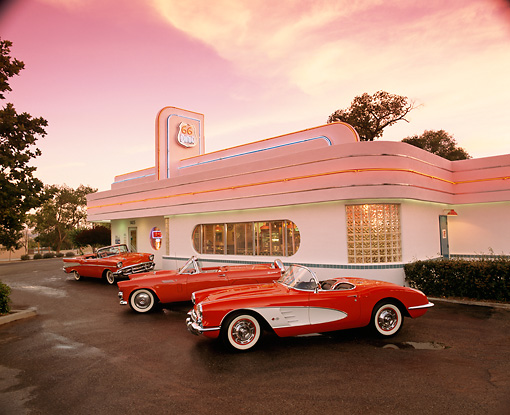 AUT 31 RK0014 01 © Kimball Stock 1960 Corvette 1956 T-Bird And 1957 Chevy Bel Air On Pavement In Front Of Diner Red Sky