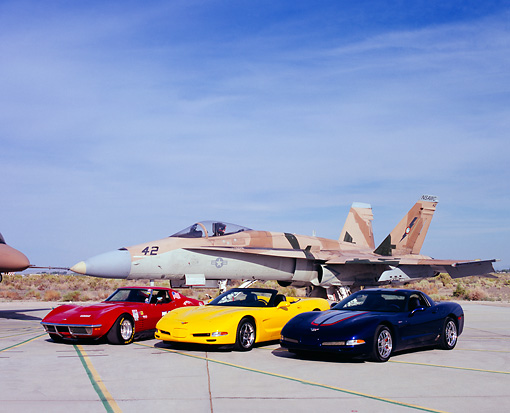 AUT 31 RK0051 05 © Kimball Stock 1970 2001 2004 Chevy Corvette Cars By Jet Fighter Airplane