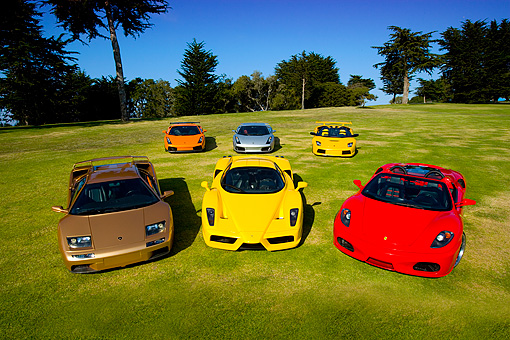 AUT 31 RK0074 01 © Kimball Stock Overhead Shot Of Six Ferrari And Lamborghini Cars On Grass