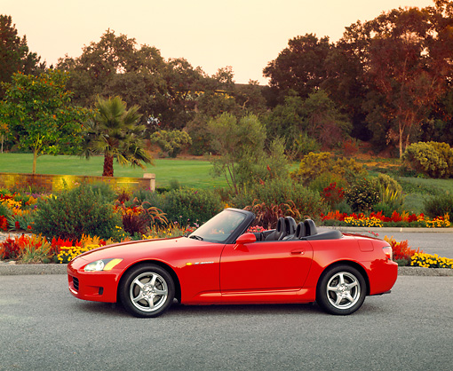 AUT 33 RK0050 02 © Kimball Stock Honda S 2000 Convertible Red Profile View On Pavement By Flowers And Trees At Dusk