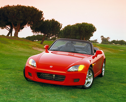 AUT 33 RK0060 01 © Kimball Stock Honda S 2000 Convertible Red 3/4 Front View On Grass Trees Background Filtered