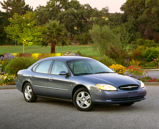 AUT 33 RK0211 02 © Kimball Stock 2000 Ford Taurus SE Blue 3/4 Front View On Pavement By Flowers And Trees