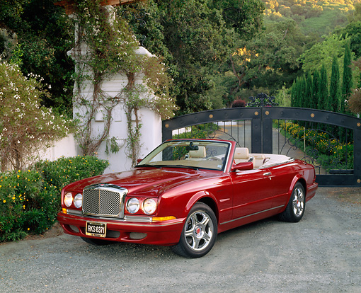 AUT 33 RK0251 02 © Kimball Stock 2000 Bentley Azure Mulliner Symbolic Edition Burgundy Front 3/4 View On Gravel By Fence And Bushes