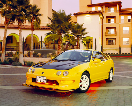 AUT 33 RK0324 02 © Kimball Stock 2000 Acura Integra Type R Yellow 3/4 Front View By Building And Palm Trees Filtered