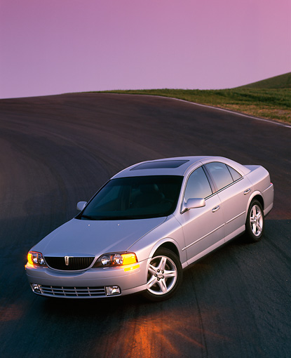 AUT 33 RK0011 06 © Kimball Stock 2000 Lincoln LS Sport Sedan Silver 3/4 Front View On Pavement Hill Filtered