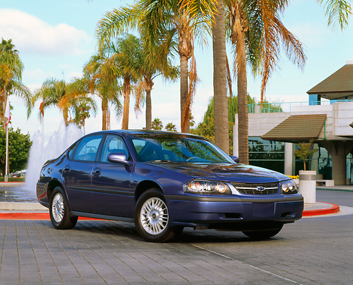 AUT 33 RK0026 02 © Kimball Stock 2000 Chevrolet Impala Blue Front 3/4 View On Pavement By Palm Trees And Water Fountain