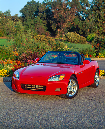 AUT 33 RK0047 02 © Kimball Stock Honda S 2000 Convertible Red Front 3/4 View On Pavement By Flowers And Trees At Dusk