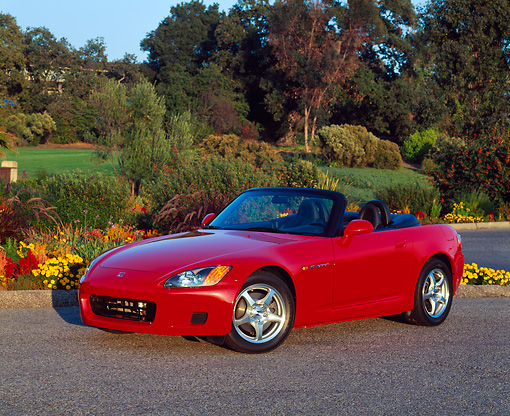 AUT 33 RK0048 01 © Kimball Stock Honda S 2000 Convertible Red 3/4 Side View On Pavement By Flowers And Trees