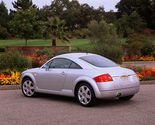 AUT 33 RK0074 04 © Kimball Stock 2000 Audi Quattro TT Coupe Silver 3/4 Rear View On Pavement By Flowers And Trees
