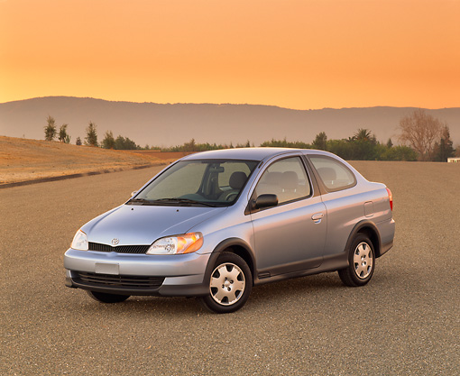 AUT 33 RK0089 05 © Kimball Stock 2000 Toyota Echo Coupe Silver 3/4 Front View On Pavement Mountains Filtered