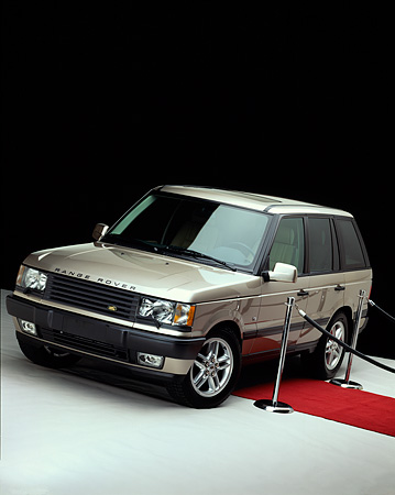 AUT 33 RK0128 06 © Kimball Stock 2000 Range Rover White Gold Front 3/4 View With Red Carpet And Poles Studio