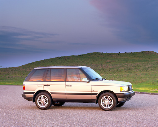 AUT 33 RK0134 02 © Kimball Stock 2000 Range Rover Gold Side View On Pavement Hills
