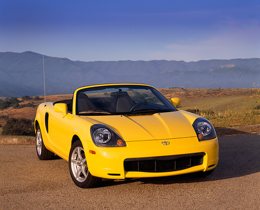 AUT 33 RK0142 07 © Kimball Stock 2000 Toyota MR2 Spyder Yellow 3/4 Front View On Pavement Dry Grass Hills