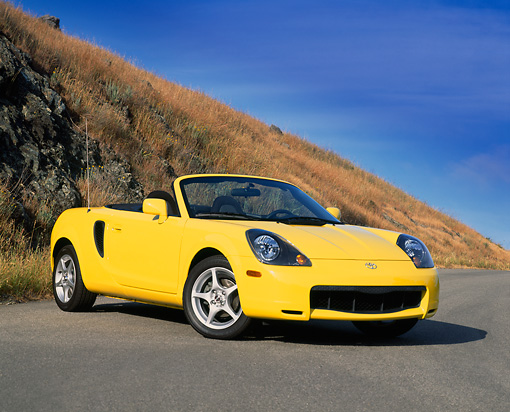AUT 33 RK0143 11 © Kimball Stock 2000 Toyota MR2 Spyder Yellow 3/4 Front View On Pavement By Dry Grass Hill