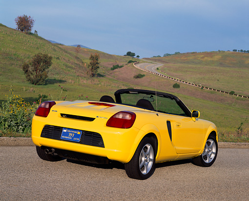 AUT 33 RK0145 01 © Kimball Stock 2000 Toyota MR2 Spyder Yellow 3/4 Rear View On Pavement By Grass Hills