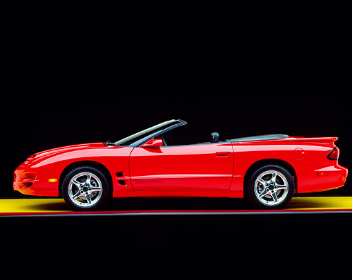 AUT 33 RK0148 04 © Kimball Stock 2000 Pontiac Firebird Trans Am WS6 Convertible Red Profile View On Yellow Floor Studio
