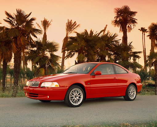 AUT 33 RK0156 11 © Kimball Stock 2000 Volvo C70 Red 3/4 Side View On Pavement By Palm Trees Filtered