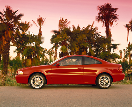 AUT 33 RK0159 01 © Kimball Stock 2000 Volvo C70 Red Profile View On Pavement By Palm Trees Filtered