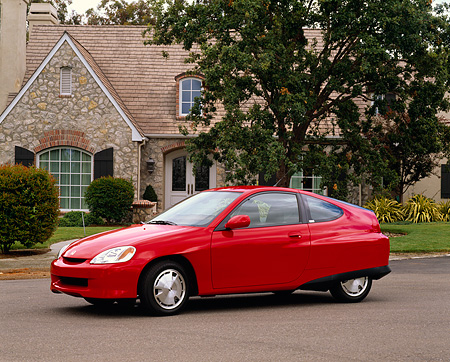 AUT 33 RK0174 02 © Kimball Stock 2000 Honda Insight Hybrid Red 3/4 Side View On Pavement By House
