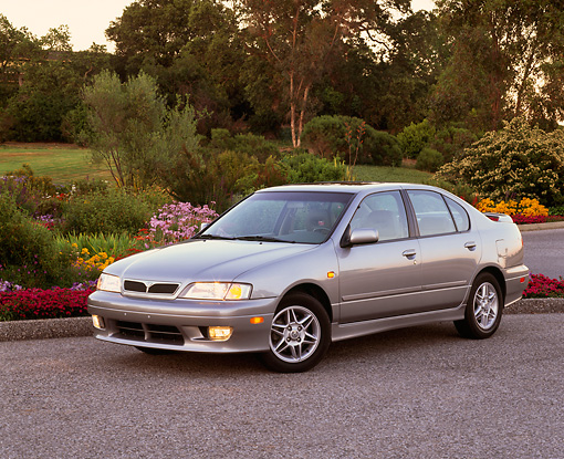 AUT 33 RK0179 14 © Kimball Stock 2000 Infiniti G20 Touring Model Silver 3/4 Side View On Pavement By Flowers