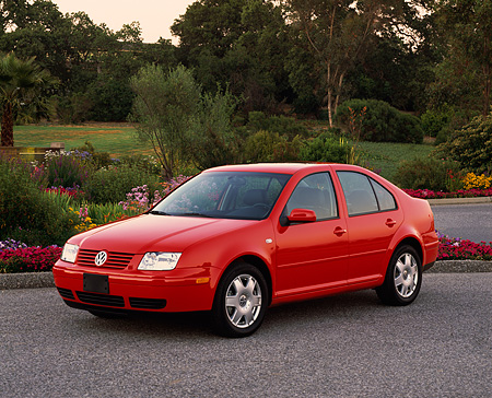 AUT 33 RK0182 03 © Kimball Stock 2000 Volkswagen Jetta Red Front 3/4 View On Pavement By Flowers And Trees