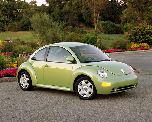 AUT 33 RK0195 03 © Kimball Stock 2000 Volkswagen New Beetle Green 3/4 Front View On Pavement By Flowers And Trees