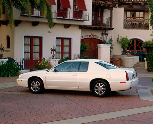 AUT 33 RK0200 03 © Kimball Stock 2000 Cadillac El Dorado Pearl White 3/4 Rear View By Spanish Building