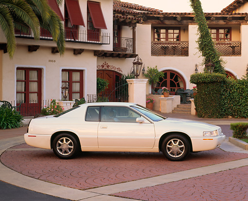 AUT 33 RK0202 05 © Kimball Stock 2000 Cadillac El Dorado Pearl White 3/4 Front View By Spanish Building