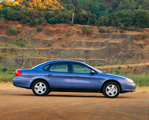 AUT 33 RK0209 02 © Kimball Stock 2000 Ford Taurus SE Blue Profile View On Dirt