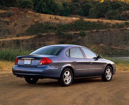 AUT 33 RK0210 07 © Kimball Stock 2000 Ford Taurus SE Blue Rear 3/4 View On Dirt By Water