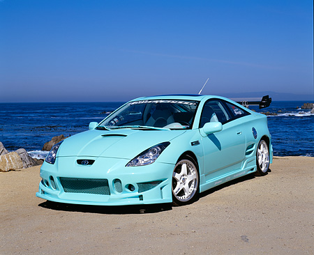 AUT 33 RK0295 09 © Kimball Stock 2000 Toyota Celica Custom Mintgreen Pearl Blue 3/4 Front View On Sand By Ocean