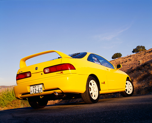 AUT 33 RK0329 01 © Kimball Stock 2000 Acura Integra Type R Yellow Low 3/4 Rear View On Pavement Blue Sky