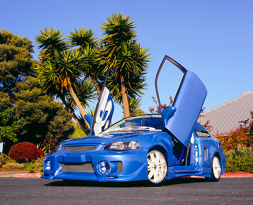 AUT 33 RK0332 01 © Kimball Stock 2000 Honda Civic Custom Blue Low 3/4 Front View On Pavement Doors Up By Palm Trees